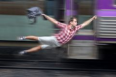 Man with backpack flies behind a moving train. Stock Photos