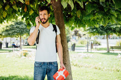 Man with backpack and a gift next to a tree stock image