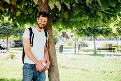 Man with backpack and a gift next to a tree royalty free stock photography