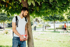 Man with backpack and a gift next to a tree royalty free stock image