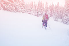 Man with backpack goes snowshoeing up a hill Stock Photos