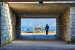 Man with a backpack goes to the pier. Mountain lake Traunsee  in Austria, Salzkammergut region.  royalty free stock images