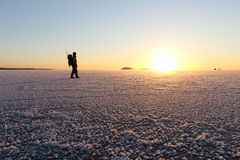 The man with a backpack going on ice on the river at sunset Royalty Free Stock Photo