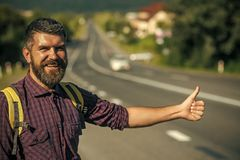 Man with backpack happy hitchhiking on road Royalty Free Stock Photos
