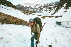 Man with backpack helmet and ice axe mountaineering. Travel Lifestyle survival concept adventure outdoor active vacations extreme sport gear wild nature snowy Royalty Free Stock Photos