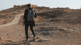 Man with backpack hiking among ancient ruins. Relaxed European male traveler walks on desert rocks and sand. Israel 4K. Man with backpack hiking among ancient stock footage