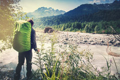 Man with backpack hiking Travel Lifestyle concept. River and mountains on background adventure vacations outdoor royalty free stock photography