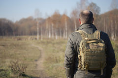 Man with a backpack on his shoulders walking on path in park Royalty Free Stock Images