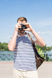 Man with backpack holding camera and photographing while standing outdoors Stock Images