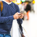 Man with backpack holding cell phone at airport Royalty Free Stock Image