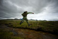 Man with backpack jumping. Man hiker jumping across small river royalty free stock photos