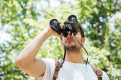 Man with backpack looking through binoculars in forest. Concentrated young man with backpack looking through binoculars in forest Royalty Free Stock Photos