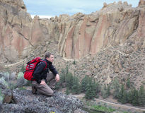 Man With Backpack Looking Over A Canyon. A man with a red backpack overlooks a canyon in climbing venue Smith Rock State Park in Oregon stock photos