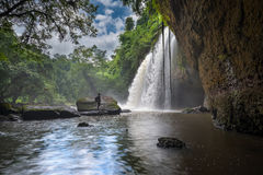 Man with backpack looking at scenic waterfall in Thailand. Man looking at beautiful waterfalls in deep forest at Haew Suwat Waterfall in Khao Yai National Park Stock Photography