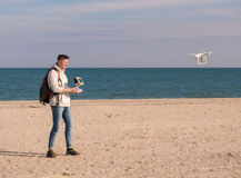 Man with backpack managing quadrocopter at a seaside Stock Photos