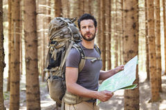 Man with Backpack and map searching directions. Beard Man with Backpack and map searching directions in wilderness area royalty free stock photo