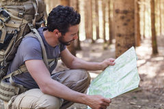 Man with Backpack and map searching directions Royalty Free Stock Photos