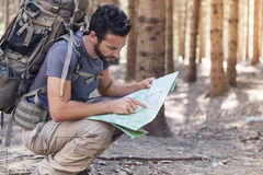 Man with Backpack and map searching directions. Beard Man with Backpack and map searching directions in wilderness area Royalty Free Stock Images