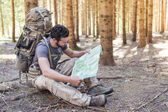 Man with Backpack and map searching directions. Beard Man with Backpack and map searching directions in wilderness area stock image