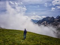 A man with a backpack is on the mountainside against the background of clouds royalty free stock photos