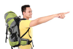 Man with backpack pointing to the direction with hand Royalty Free Stock Photography