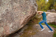 Man with backpack pushing a huge stone. Man with backpack pushing huge stone Royalty Free Stock Images