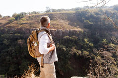 Man with backpack. Rear view of senior man with backpack standing on top of the mountain stock photo