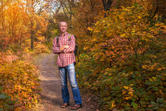 Man with backpack relaxing in a autumn forest . Royalty Free Stock Images