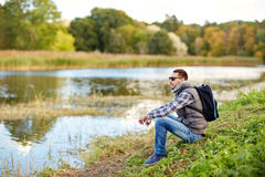 Man with backpack resting on river bank Royalty Free Stock Photos