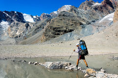 Man with backpack resting on trekking pole moves a river Royalty Free Stock Image