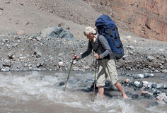 Man with backpack resting on trekking pole moves a river Stock Photos