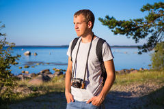 Man with backpack and retro camera on the beach Royalty Free Stock Photos