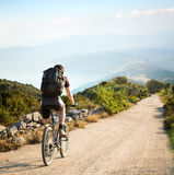 Man with Backpack Riding a Bicycle in Mountains Stock Photos