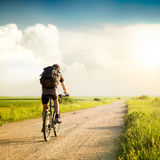 Man with Backpack Riding a Bicycle Royalty Free Stock Photography