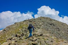 A man with a backpack rises to the top of the mountain. A man with a backpack rises to the top of the mountain stock image