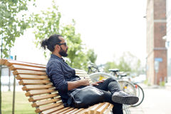 Man with backpack sitting on city street bench Stock Photos