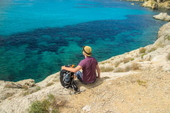 Man with backpack sitting on cliff above sea Royalty Free Stock Image