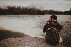 Man in Backpack Sitting by the Edge of Rock Taking a Photo of a Waterfall Royalty Free Stock Images