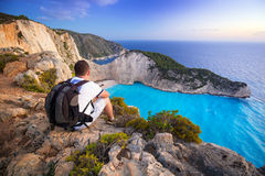 Man with backpack sitting watching sunset over Navagio beach on Zakynthos Royalty Free Stock Photos