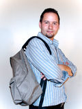 Man with a backpack. A man is standing with a brown backpack with folded arms in gray shirt Royalty Free Stock Photography