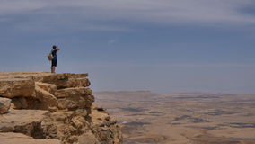Man with backpack standing on the desert mountain rock cliff edge. Professional shot in 4K resolution. 101. You can use it e.g. in your commercial video Royalty Free Stock Photo
