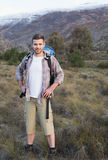 Man with backpack standing on forest landscape Stock Photos