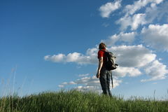 Man with the backpack. A man with a backpack, standing in the grass against the sky. Rear view Royalty Free Stock Images