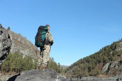 The man with a backpack standing at the mountain river. The traveler with a backpack standing on sand at the rocky river bank stock photo