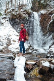 Man with backpack standing near waterfall at mountains in winter. Portrait of attractive bearded young man with backpack standing near waterfall in mountains in Royalty Free Stock Images