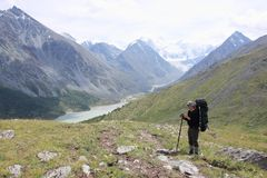 Man with a backpack standing on the pass Kara-Turek, Altai Mountains, Russia. Man with a backpack standing on the pass Kara-Turek, view of the Akkem Lake, Altai stock images