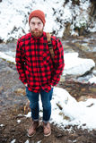 Man with backpack standing in winter forest near mountain river. Top view of handsome bearded young man with backpack standing in winter forest near mountain Royalty Free Stock Photos
