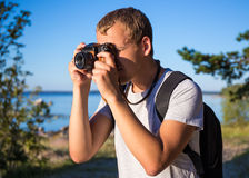 Man with backpack taking a photo with retro camera on the beach Stock Photography