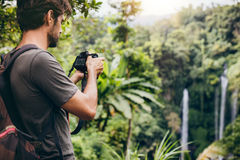 Man with backpack taking a photo of waterfall Royalty Free Stock Image