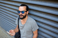 Man with backpack texting on smartphone in city Stock Image